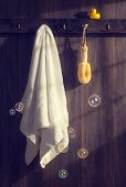 White towel with loofah hanging on wall with floating bubbles and sunlight filtering through - vinta