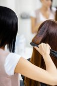Backview of hairdresser doing hair style for woman in hairdressing salon. Concept of fashion and bea