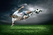 stock photo of football  - Football player with ball in action under rain outdoors - JPG