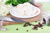 Composition with fresh and marinated cabbage (sauerkraut), spices, on color napkin background