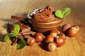 Sweet chocolate hazelnut spread with whole nuts and mint on wooden background