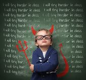 stock photo of discipline  - Naughty devil schoolboy with lines written on a blackboard reading I will try harder in class and devils horns - JPG