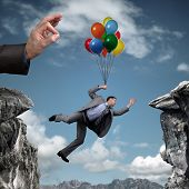 Businessman holding on to balloons above a cliff trying to escape hand bursting his balloon and brid