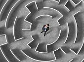 stock photo of daring  - Top view of businessman standing in center of labyrinth - JPG