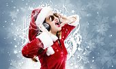 Young attractive Santa girl listening music in headphones