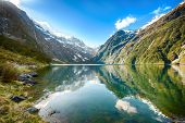 Peaks of Darran Mountains reflecting in a Lake Marian, Fiordland national park, New Zealand South is
