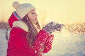 stock photo of joy  - Beauty Winter Girl Blowing Snow in frosty winter Park - JPG
