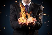 Businessman with fire in hands. Concept of threats and manager responsibility