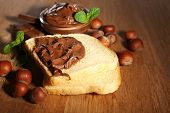 Bread with sweet chocolate hazelnut spread on wooden background