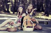 stock photo of hippy  - Hippie girls with guitar sitting on the road - JPG