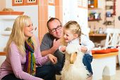 Parents and daughter rocking and playing with rocker horse in living room
