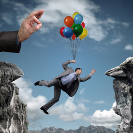 stock photo of adversity humor  - Businessman holding on to balloons above a cliff trying to escape hand bursting his balloon and bridge the gap concept for business adversity - JPG