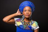 stock photo of traditional attire  - attractive south african woman in traditional attire looking up on black background - JPG