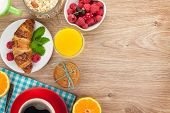 Healty breakfast with muesli, berries, orange juice, coffee and croissant. View from above on wooden table with copy space