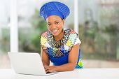 picture of zulu  - modern african zulu woman with laptop computer at home - JPG