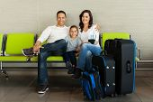 portrait of family with luggage waiting at airport