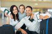 stock photo of boarding pass  - happy family holding boarding pass and passport at airport - JPG