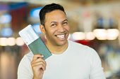 cheerful mid age man holding passport and boarding pass at airport