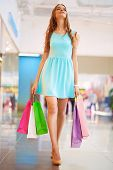 Pretty young shopper with shopping bags walking down mall
