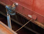 Welder In Man Lift Welding On Ship Hull