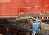 Men In Lift Guiding Steel Plate