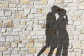 Silhouette Of Kissing Couple, Against Natural Stone Wall