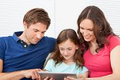 Family Using Digital Tablet On Sofa