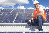 stock photo of roofs  - Solar panel technician on roof with solar panels - JPG