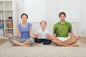 Family Practicing Yoga At Home
