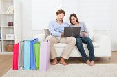 Couple Shopping Online With Bags On Sofa At Home