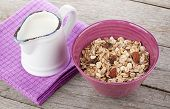 Healty breakfast with muesli and milk. On wooden table