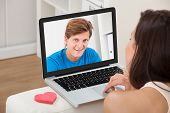 Woman Video Chatting With Boyfriend On Laptop At Home