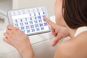 stock photo of menstruation  - Cropped image of young woman using calendar on digital tablet at home - JPG
