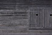 stock photo of prank  - dark colored wooden window framed by wooden pranks - JPG