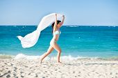 Woman With Sarong Running On Beach