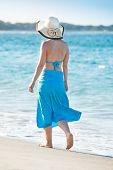 Woman Wearing Sunhat Walking On Beach