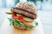 stock photo of beef-burger  - Lean beef burger with rocket pickles tomato and onions