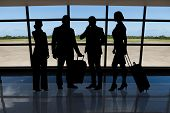 Businesspeople With Luggage Standing Against Airport Window