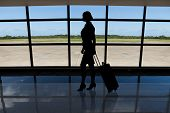 Businesswoman With Baggage Walking Against Airport Window