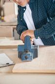 Midsection of carpenter working with electric planer in workshop