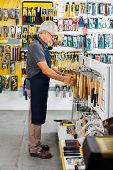 Full length side view of senior salesman working in hardware store