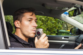 picture of youg  - Youg man in car looking at breathalyzer - JPG