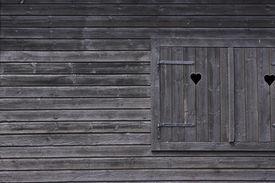 stock photo of prank  - dark colored wooden window framed by wooden pranks - JPG