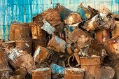 Old Pile Of Rusty Paint Cans Against Wall