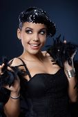 Happy beauty posing in glamorous outfit, sequin hat and feather boa, fancy dress and accessories.