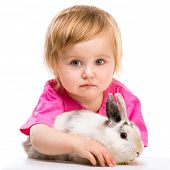 baby girl in a pink T-shirt with her small white rabbit  on white background