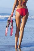 Rear view of beautiful young woman in red bikini with snorkel, mask & flippers on a deserted beach with blue sky