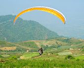 foto of parachute  - people is trying to control his parachute to the sky in Paragliding sport - JPG