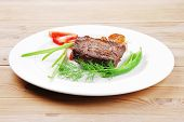 meat savory : grilled beef fillet mignon served on white plate over wooden table with chili pepper and tomatoes