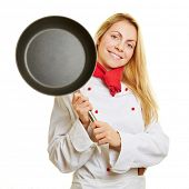 Smiling young female chef cook holding a frying pan